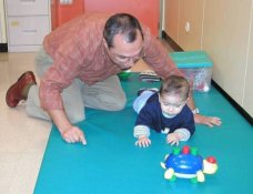 Photo. A practicioner is assessing a low vision baby who is tracking a moving toy